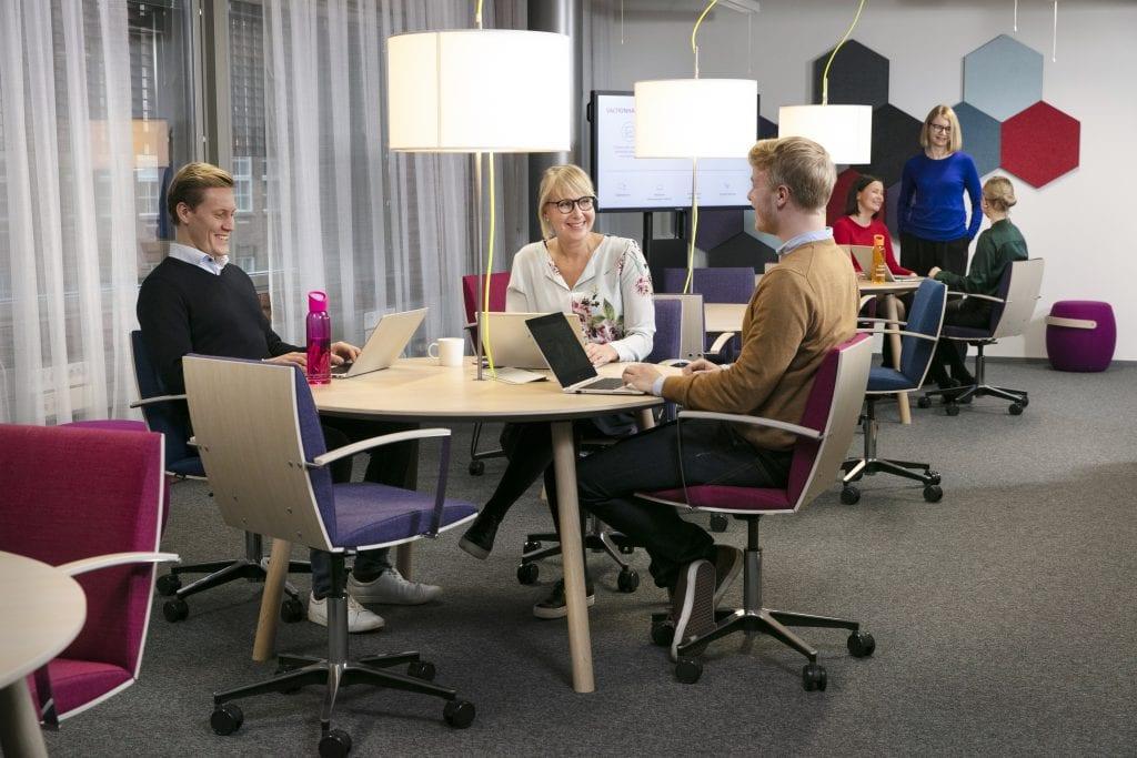 ihmisiä ryhmätyössä pyöreän pöydän ääressä