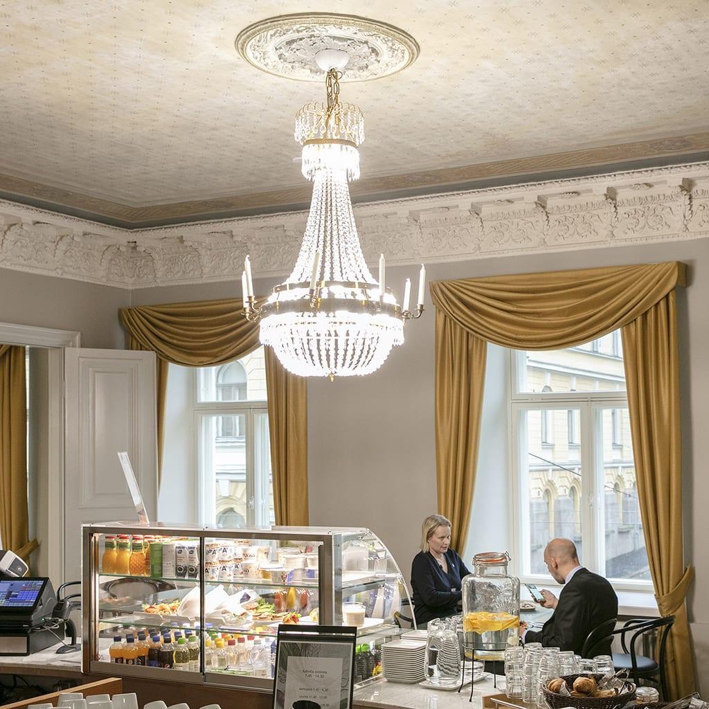 ministeriön kahvio jossa suuri kristallikruunu, mies ja nainen tiskin edessä