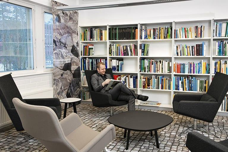 mies lukunurkkauksessa, kirjahylly ja nojatuoleja