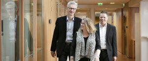 Aarne Hiltunen, Raija Haapiainen ja Mika Hillberg kävelevät toimiston käytävällä