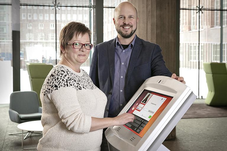 Henna Köntti ja Marko Kääriä aulan virtuaaliaulapalvelu automaatilla