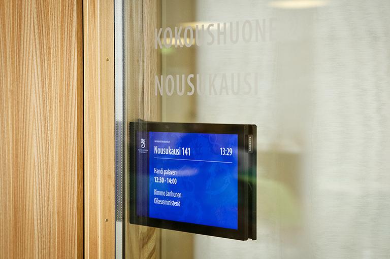 pieni infonäyttö kokoustilan ovenpielessä