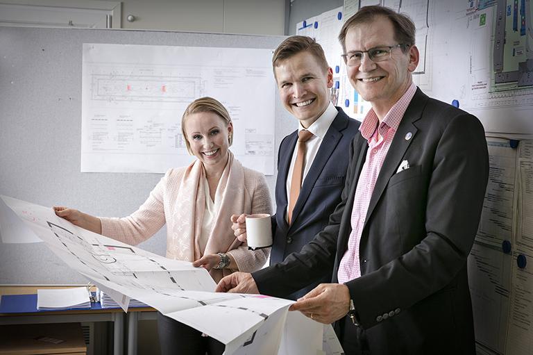Anna, Heikki ja Markku katsovat hymyillen kameraan kädessään iso pohjapiirros