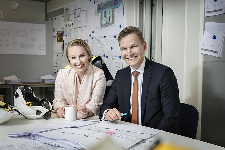 Anna ja Heikki pöydän äärellä, jossa rakennuspapereita ja kaksi valkoista kypärää.
