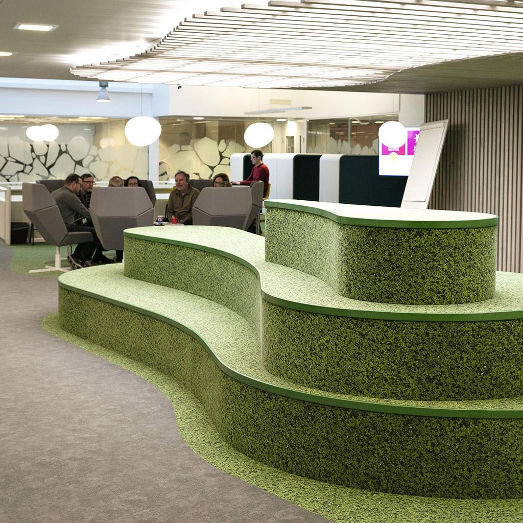 vihreä kaareva 3-kerroksinen elementti, taustalla työpisteitä.