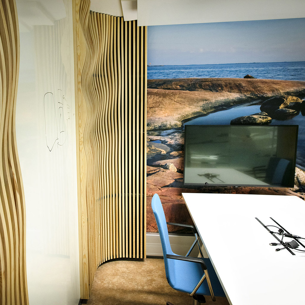 Neuvotteluhuoneen pöytä ja näyttö, aaltoilevaa puuritilää seinällä, maisemakuva toisella seinällä.