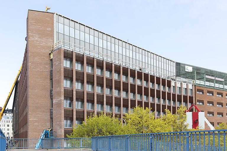 Punatiilinen toimistotalo, edessä puunlatvoja ja sinistä sillankaidetta.
