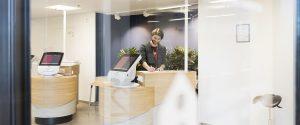 asiakaspalvelutilassa itsepalvelutiskejä, mies kirjoittaa yhdellä tiskillä.