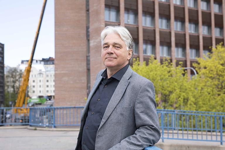 Petri Turku seisoo ulkona kävelysillalla, taustalla uusi toimistorakennus.