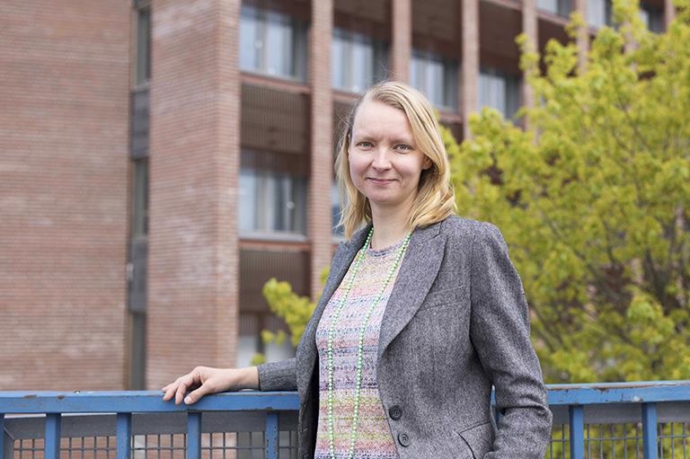 Sonja Nybonn nojaa ulkona kävelysillan siniseen kaiteeseen, taustalla toimistorakennusta.