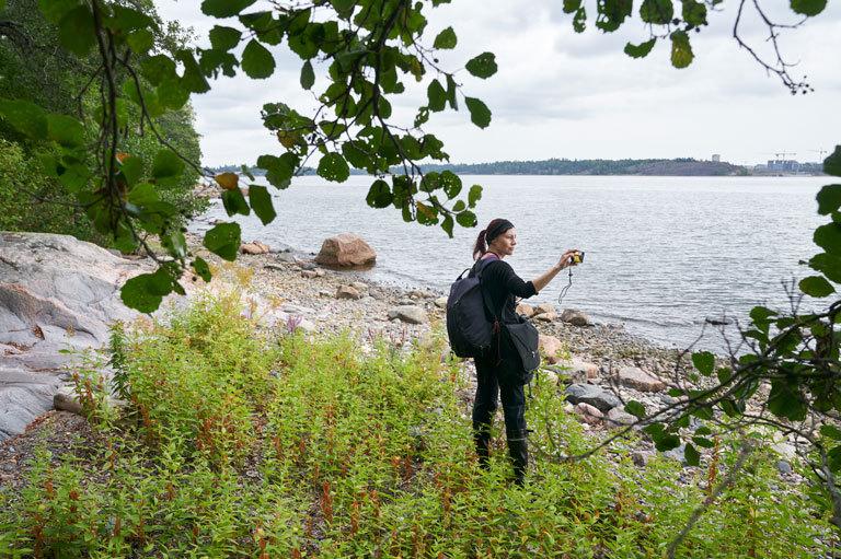 Elina Manninen rannalla kuvaamassa digikameralla.