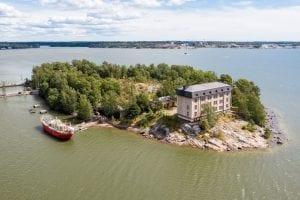 Ilmakuva Hylkysaaresta jossa kasarmirakennus ja rannalla laiva.