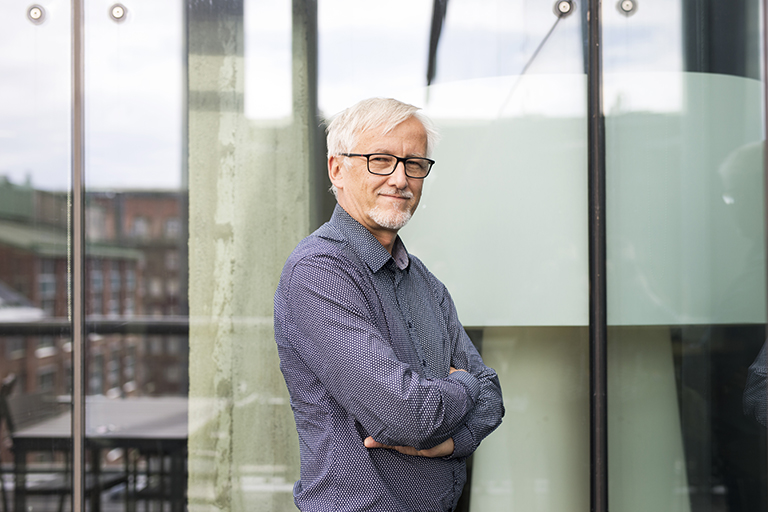 Matti Salminen seisoo isojen lasi-ikkunoiden edessä.