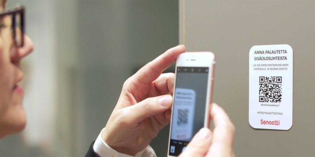 Henkilö skannaa QR-koodia älypuhelimella.