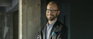 Mikko Ahola seisoo toimistoympäristössä.
