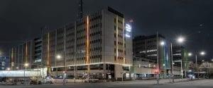 Havainnekuva, jossa Värivuoto-valotaideteos näkyy rakennusten seinissä yöllä Helsingin Pasilassa.
