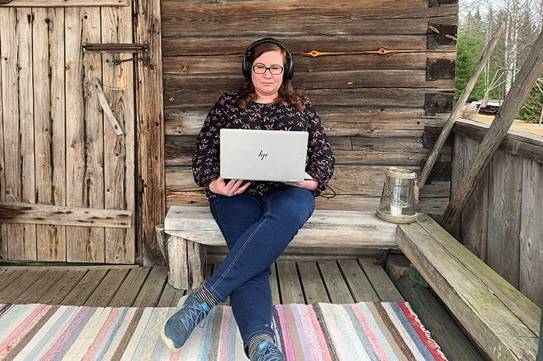 Jenni Kotilainen istuu rantasaunansa terassilla työkoneen ja kuulokkeiden kanssa.