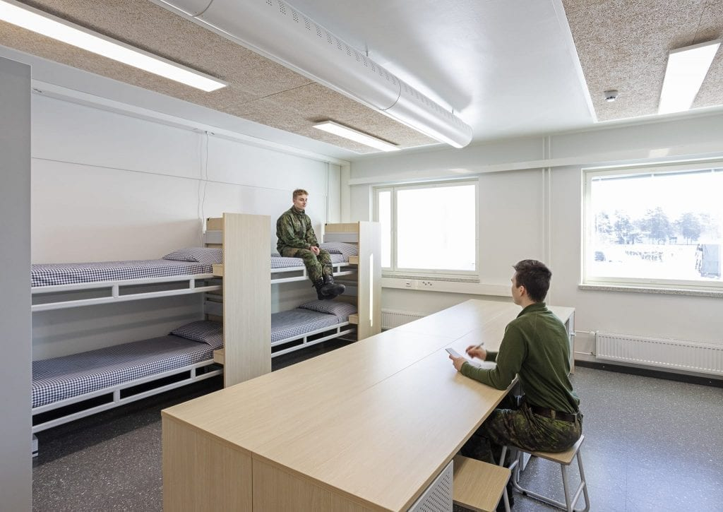 uusi varusmiesten tupa, jossa keskellä työpöytä ja uudenlaiset kerrossängyt.