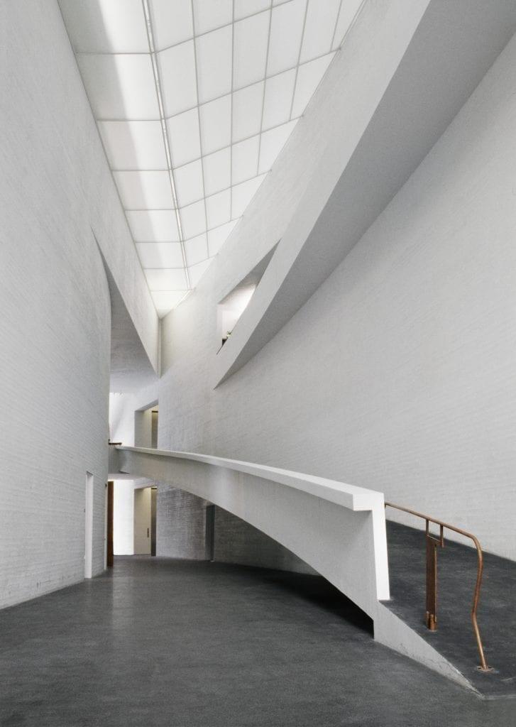 Korkea tila, jossa on valkoiset seinät. Lattia on tummanharmaata betonia. Kaareva ramppi johdattaa aulasta rakennuksen toiseen kerrokseen. Tilassa ei ole ihmisiä..