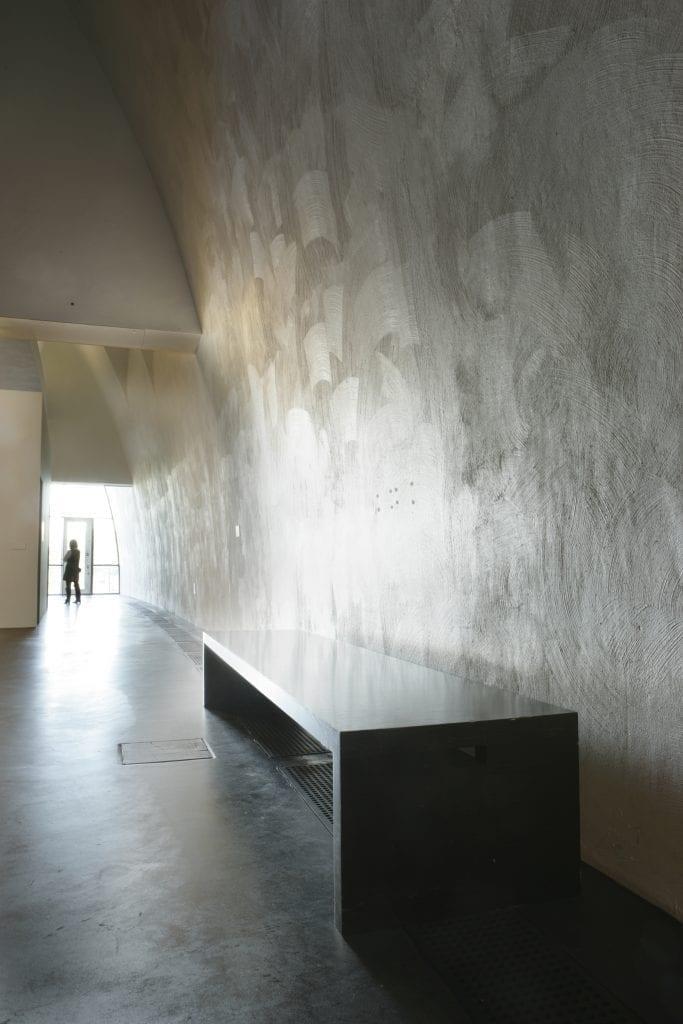 Huone, johon tulee valoa sen toisesta päästä. Etäisyydessä näkyy ihmisen silhuetti. Seinien pinnoissa erottuu selvästi kaarevia jälkiä. Seinän edustalla on suorakulmainen tumma penkki.