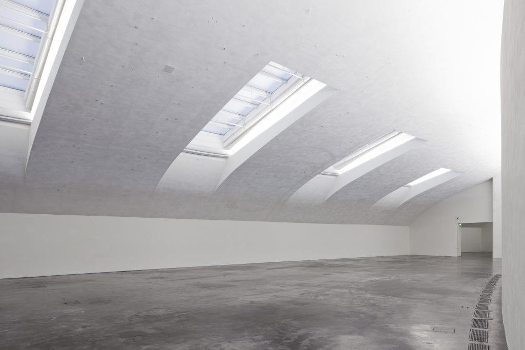Pitkä, valkoinen huone, jossa on kaartuva katto. Katossa on neljä isoa kattoikkunaa. Ikkunoiden päällä on ohuet, verkkomaiset verhot.