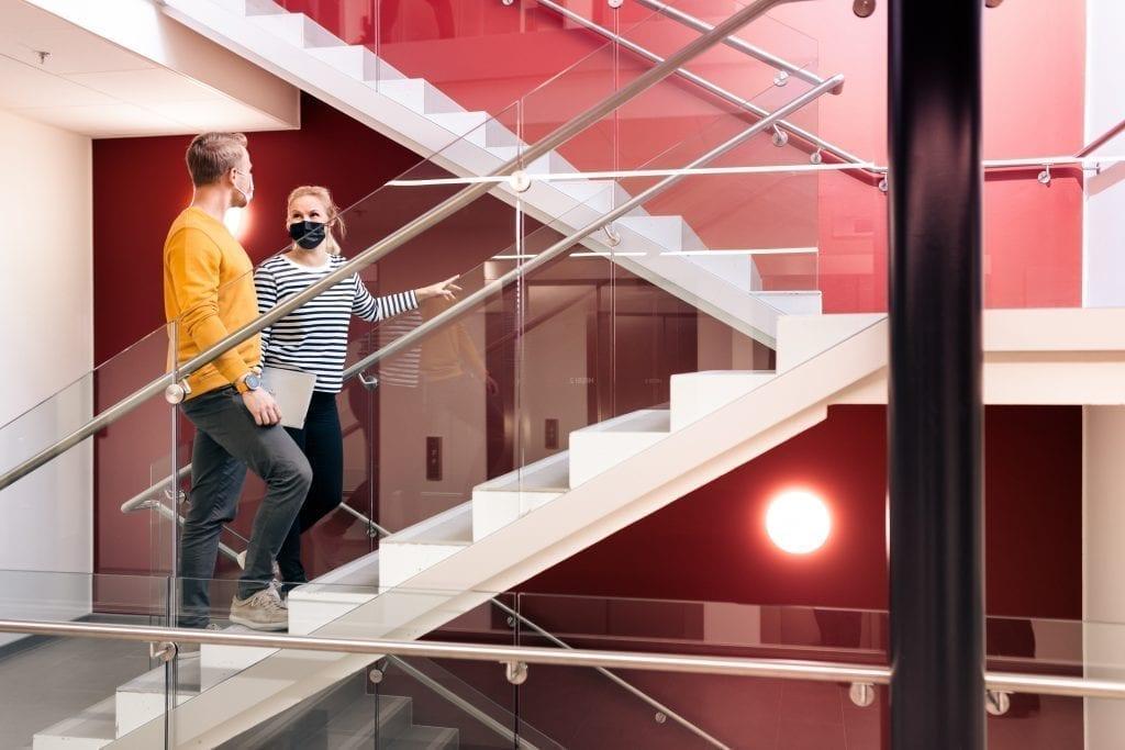 Mies ja nainen käveletä toimiston portaita.