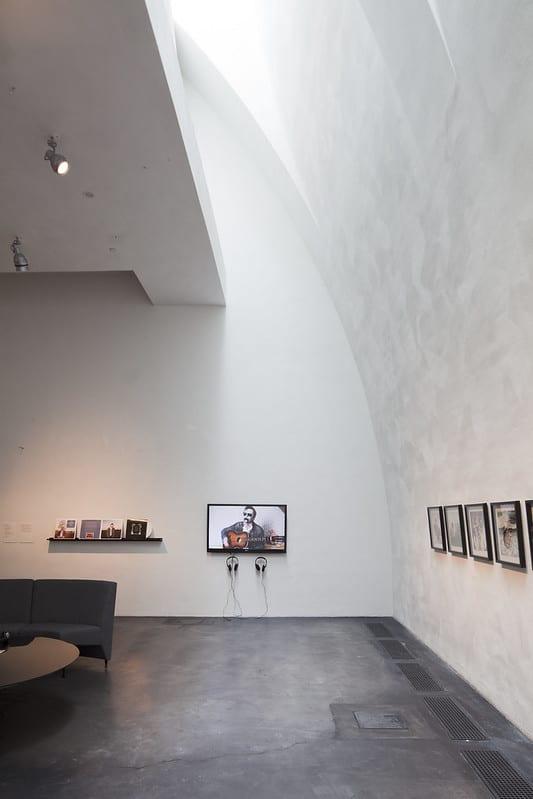 Kiasman kolmannen kerroksen galleriatila. Valo lankeaa sisään rakennuksen kaksoiskaarevan itäsivun rusetti-ikkunoista. Valkoisen seinän pinta on eläväinen, siinä näkyy kaareva rappausjälki. Esillä on Petri Ala-Maunuksen teoksia vuoden 2012 Thank You for the Music -näyttelyssä.