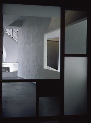 Lasioven metalliset tukirakenteet hahmottuvat tummina. Käytävätila, jonka perällä näkyy kierreportaiden kulma. Seinässä on ikkuna-aukko rakennuksen sisätiloihin.
