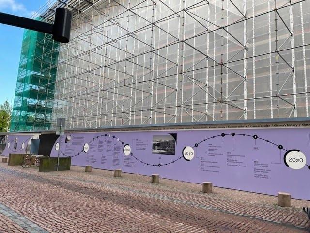 Rakennustelineiden peittämä rakennus. Rakennustelineiden edessä on aita, jossa on violetille pohjalle kuvattu graafisien elementtien ja valokuvien avulla aikajana.