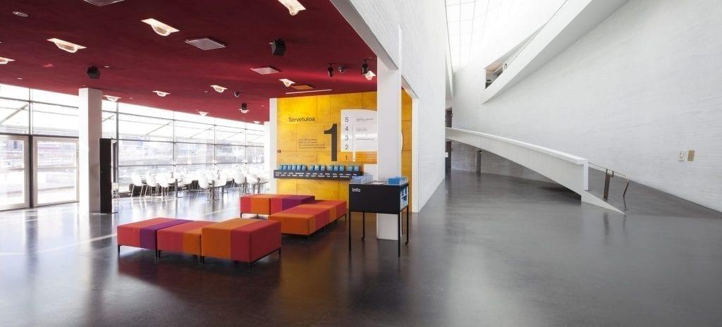 Kiasman aula. Vasemmalla puolella kuvaa avautuu näkymä Kiasman punakattoiseen ravintolasaliin, oikealla puolella näkyy näyttelytiloihin vievä veistoksellinen ramppi ja valkoiseksi maalatut korkeat seinät ja kattoikkuna.