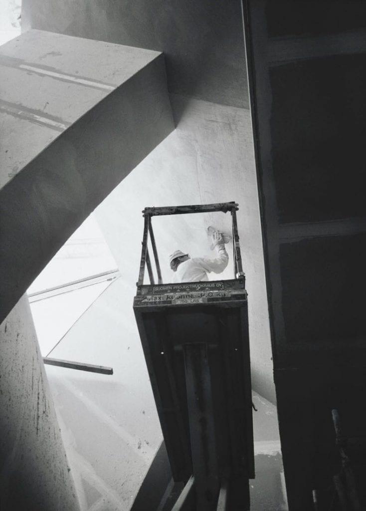 Mies seisoo henkilönostimella, joka on nostettu katonrajaan. Sama valkoiseen haalariin ja lakkiin pukeutunut mies rappaa seinää.