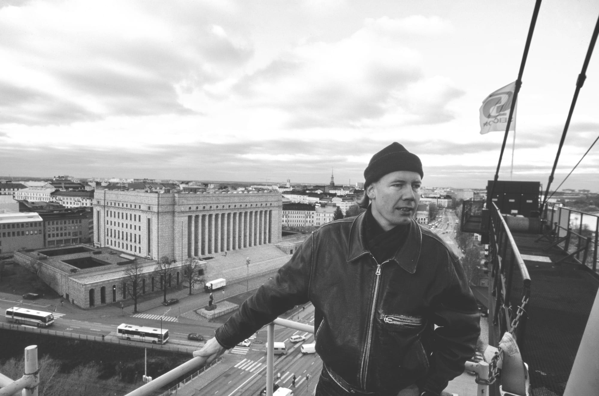 Arkkitehti Timo Kiukkola nosturissa, taustalla näkyy Eduskuntatalo ja Etu-Töölöä. Mannerheimintiellä ajaa autoja.