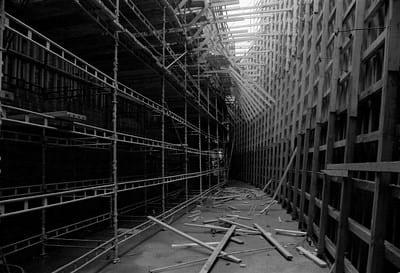 Rakennustelineitä ja lautarakennelmia. Keskeltä lähtee käytävä, joka näyttää kapenevan ja kääntyvän. Lattialla on lautoja sikin sokin, ylhäältä kajastaa päivänvalo.