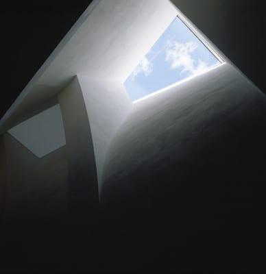 Seinän kaarevat muodot vievät katseen kohti puolikkaan rusetin muotoista ikkunaa. Ikkunasta näkyy haituvaisia pilviä ja sininen taivas.