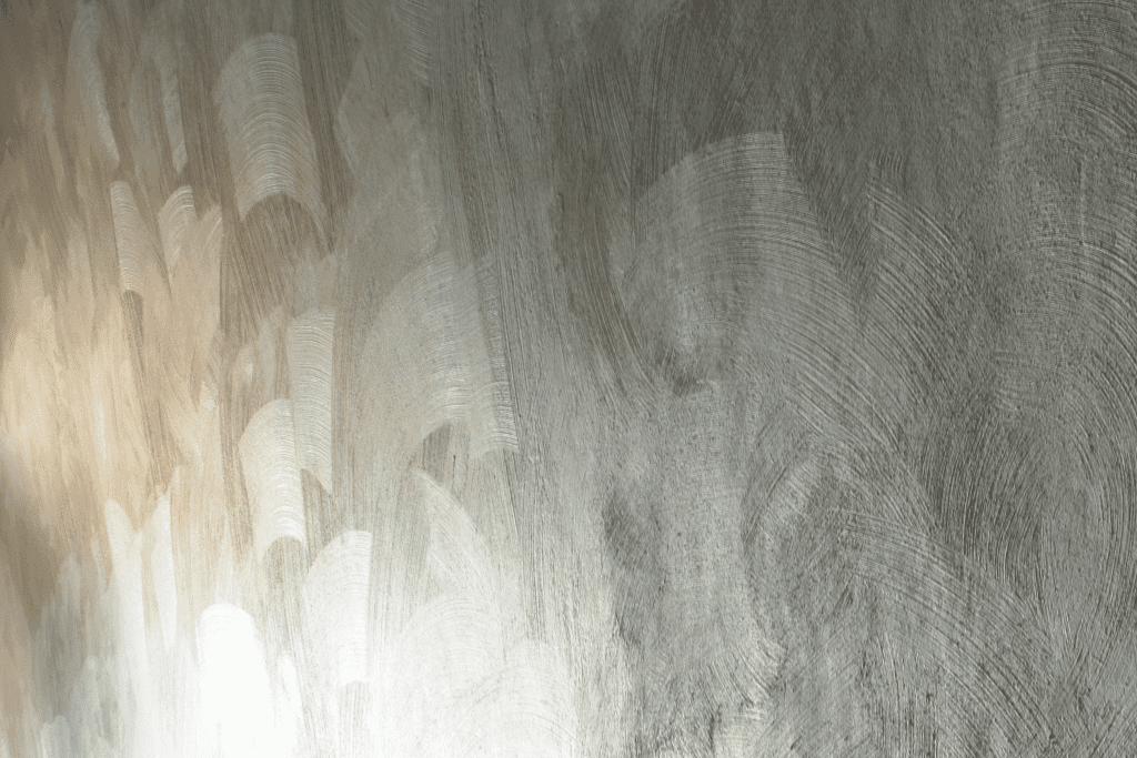 Puolilähikuva Kiasman gallerioiden seinätilojen rappauksesta. Sivusta tuleva valo leikittele rappauspinnan kaarevilla kuvioilla.