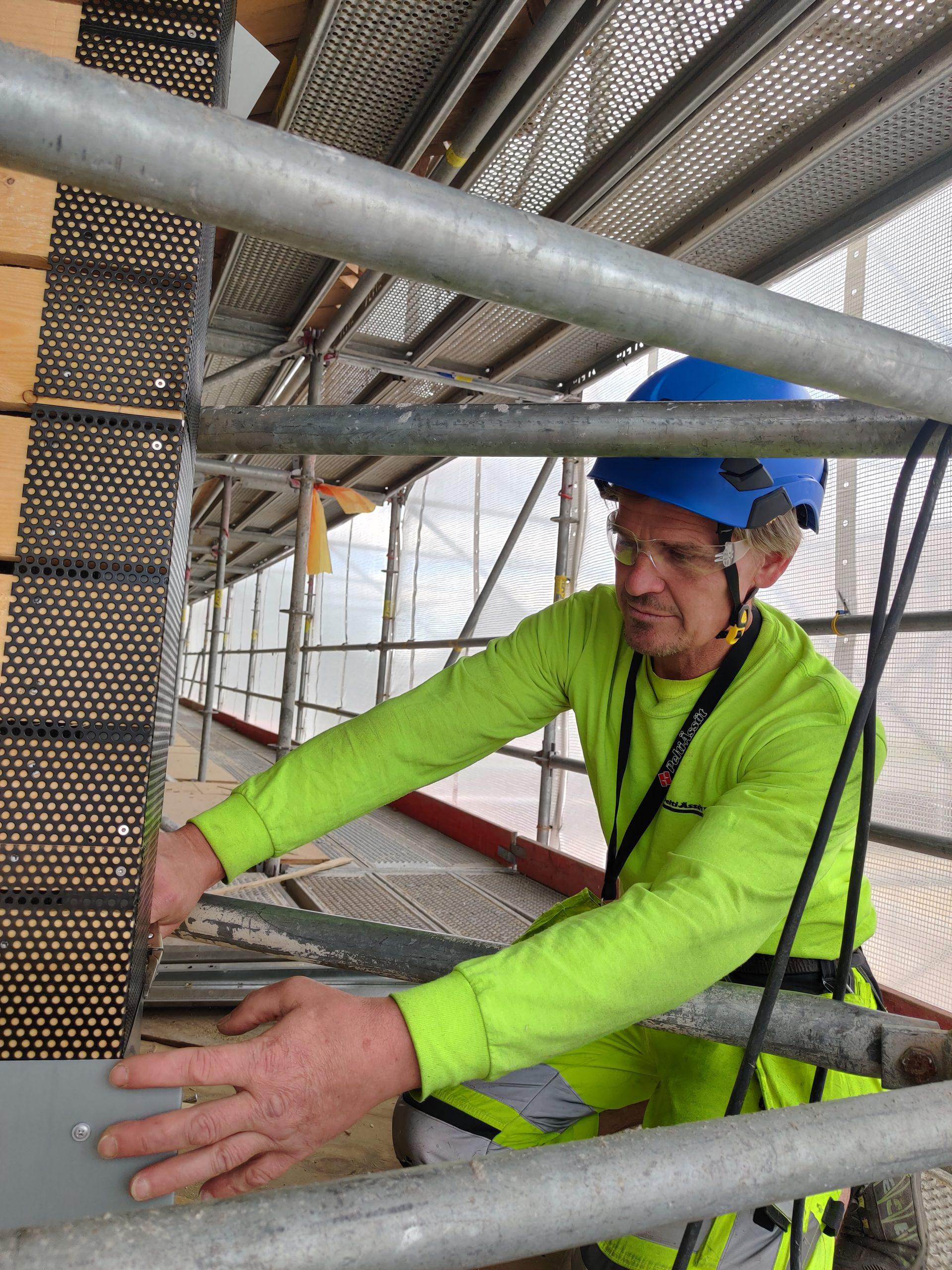 Mies polvistuneena rakennustelineillä asentamassa peltiä rakennuksen kulmaan.