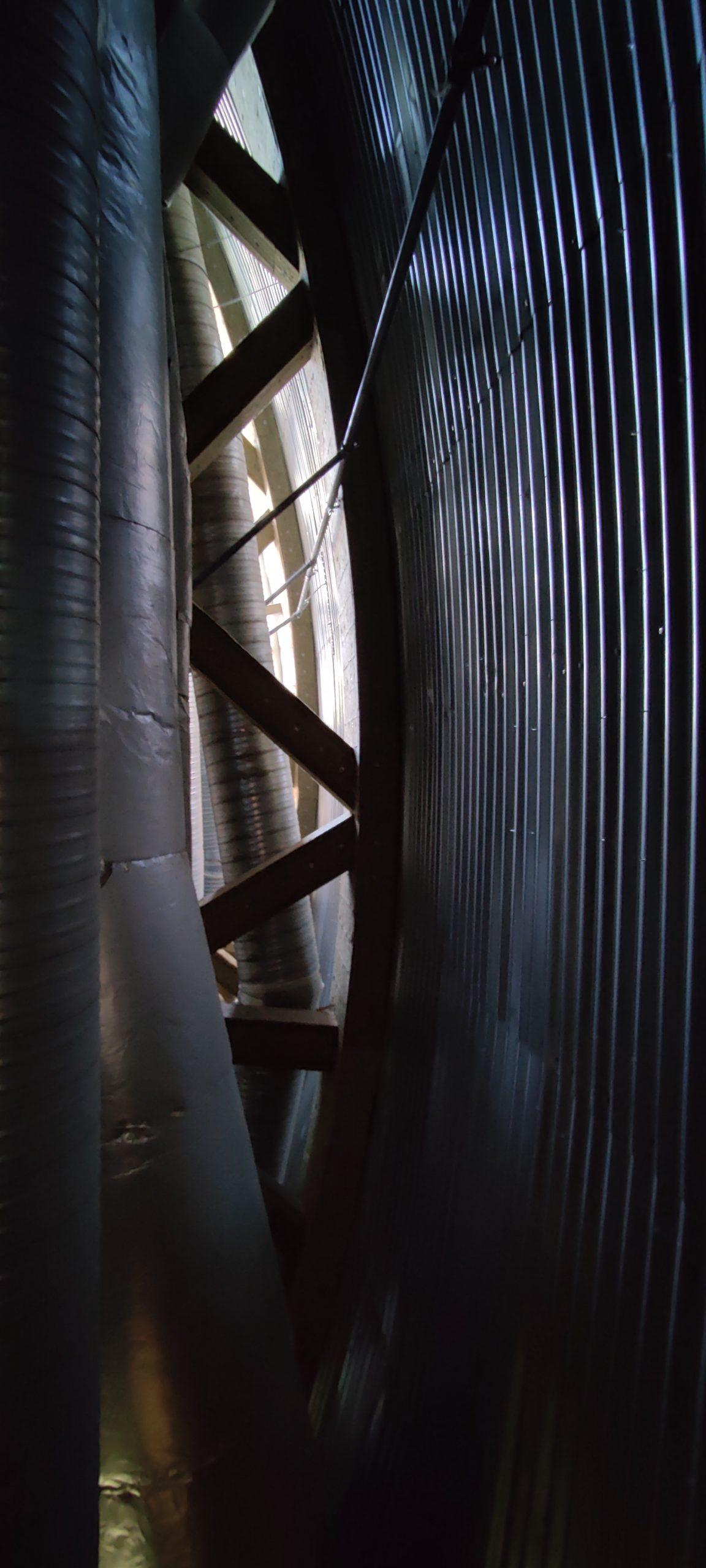 Kaareva aaltopeltiseinä, putkia ja tukevia ristikkorakenteita.