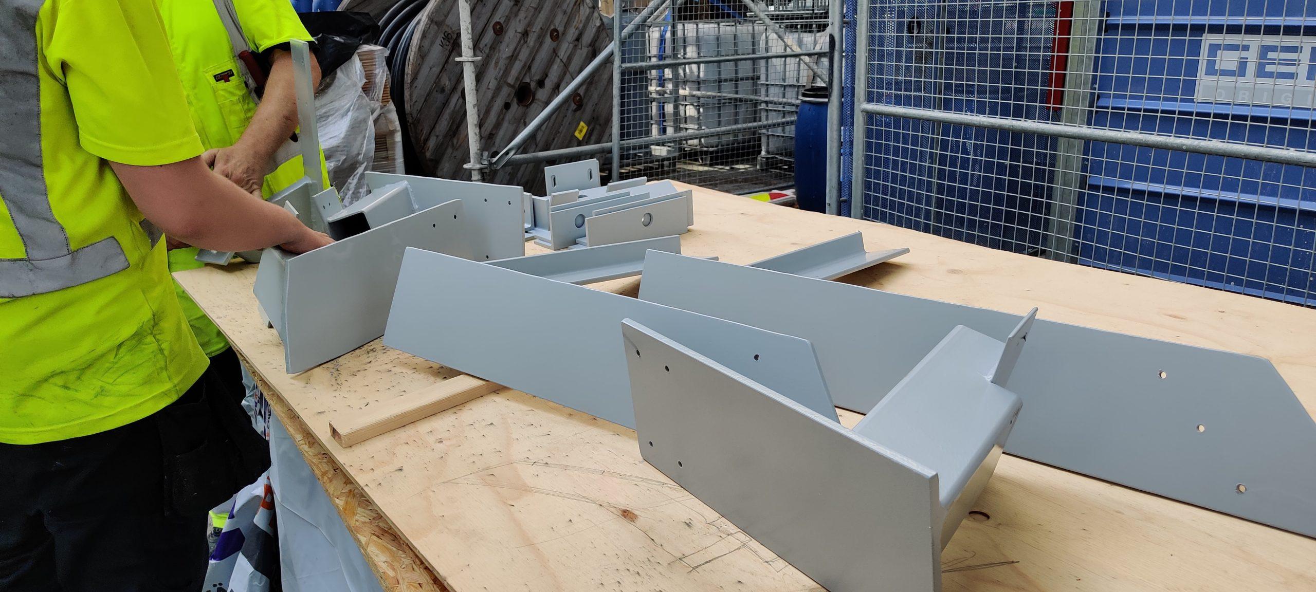 Harmaita metallisia rakenteita lastulevypöydällä.