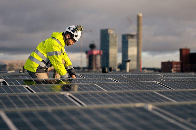Aurinkopaneelien asennusta rakennuksen katolla