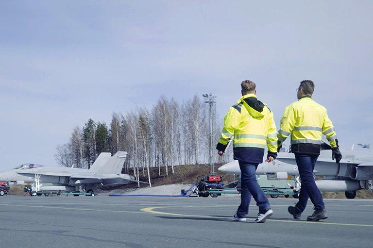 Kaksi miestä kävelee kiitoradalla, taustalla Boeing F/A-18 Hornet -monitoimihävittäjiä
