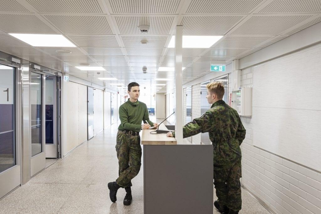 Kaksi henkilöä armeijan vaatteissa keskustelee käytävällä.