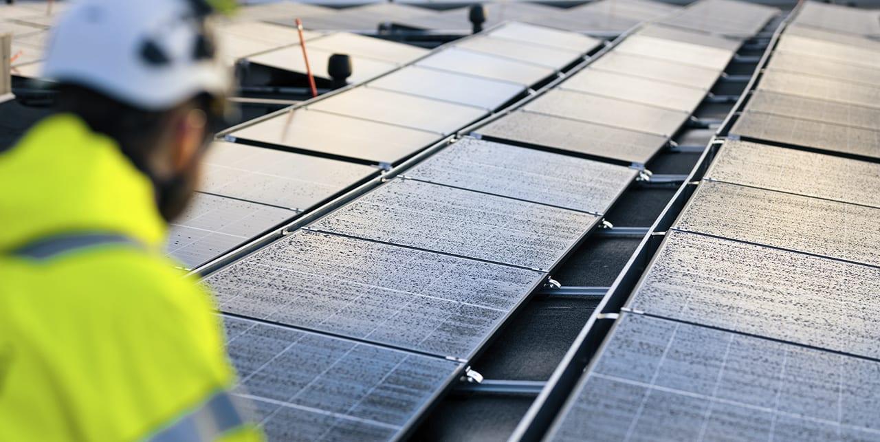 Työntekijä tarkistaa aurinkopaneeleja rakennuksen katolla.