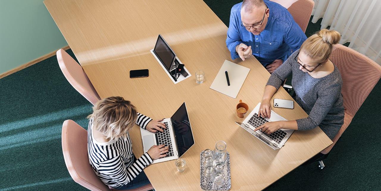 Kolme henkilöä työskentelee pöydän ääressä kannettavien tietokoneiden kanssa.