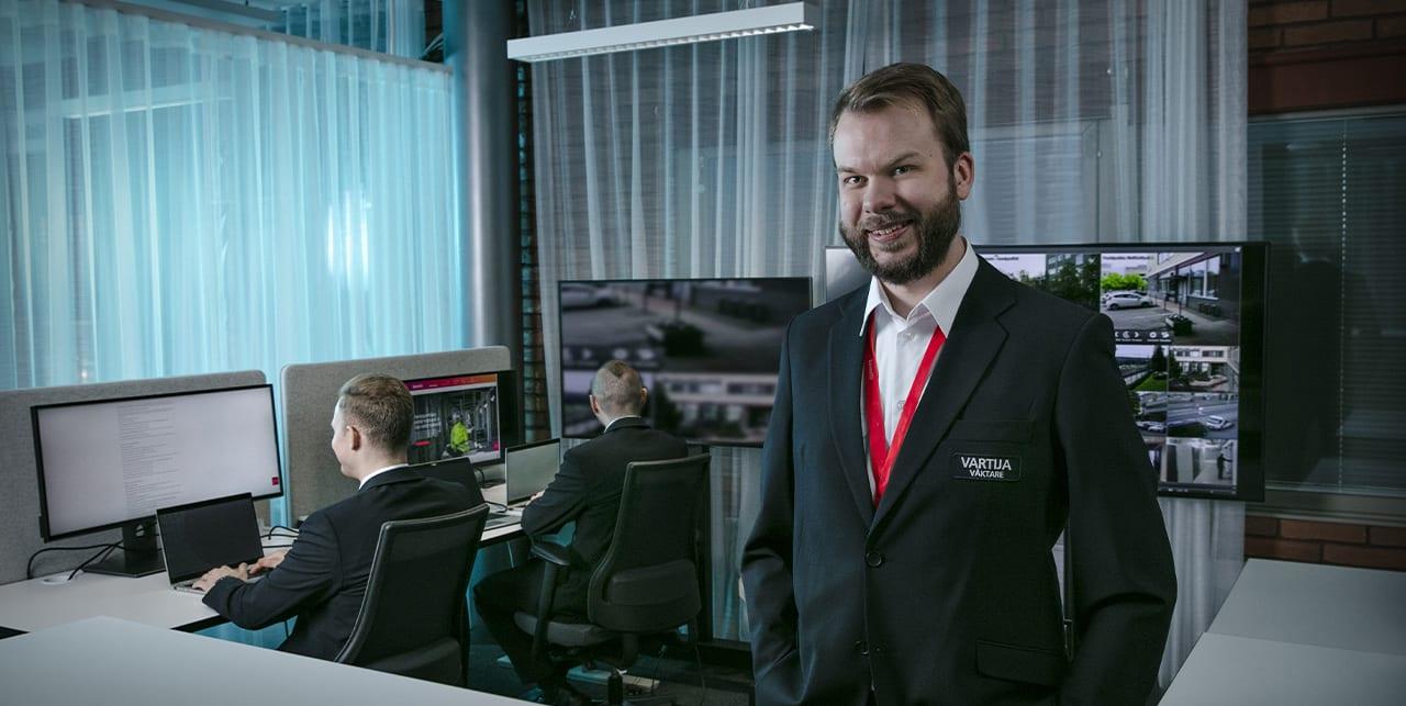 Henkilö vartijan asussa hymyilee kameralle samalla kun kaksi henkilöä taustalla työskentelee tietokoneilla.