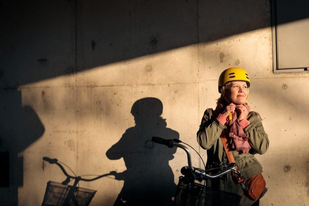 Henkilö kiinnittää pyöräkypärää seisoessaan polkupyörän vieressä.