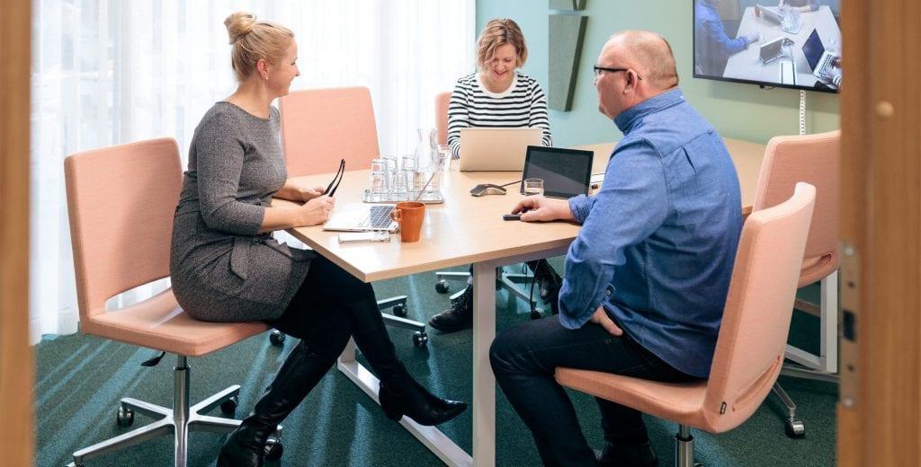 Kolme henkilöä työskentelee pöydän ympärillä