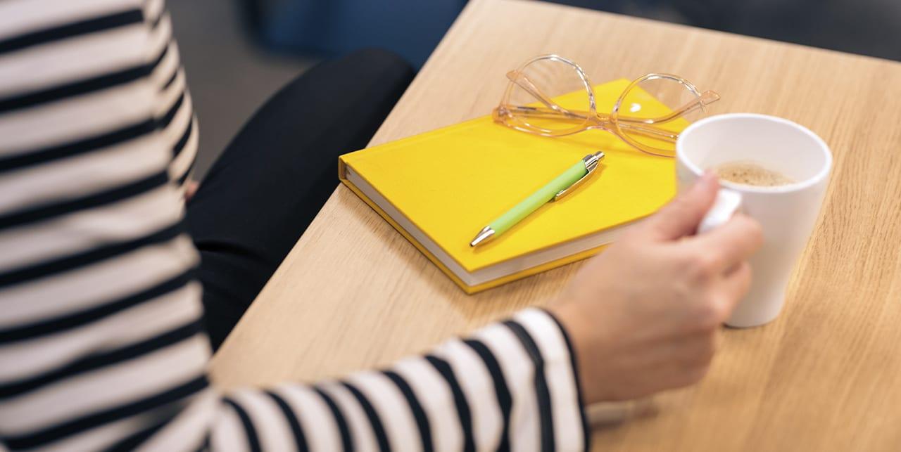Kahvikuppi ja muistikirja pöydällä